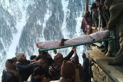Residents move the body of a victim who died after a heavy snowfall in Seri Village in Neelum Valley