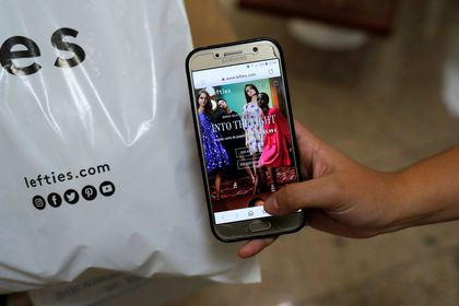A customer shows the new Lefties online shop website on a mobile phone outside a Lefties store, an Inditex brand, in Malaga