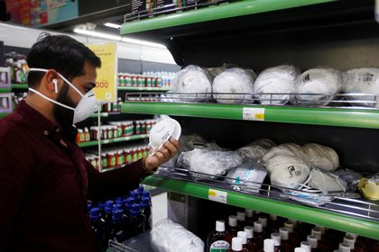 An Iraqi man wears protective mask, following the outbreak of the coronavirus, as he looks at face masks at a supermarket in Baghdad