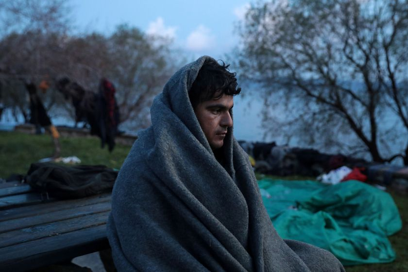 A migrant, who arrived the previous day on a dinghy after crossing part of the Aegean Sea from Turkey, is covered with a blanket near the village of Skala Sikamias, on the island of Lesbos