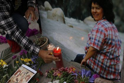 A man places a lit candle next to an image of environmental and Indigenous rights activist Berta Caceres at a spiritual ceremony, a day before a trial against one of the alleged masterminds of the killing of Caceres, in Tegucigalpa, Honduras, Monday, April 5, 2021. The trial of Roberto David Castillo is expected to run through April. The government has already convicted seven people in Caceres' murder, but is Castillo is considered a potentially critical link to those who ordered it. (AP Photo/Elmer Martinez)