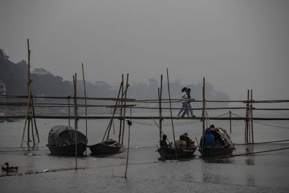 Indian girls walk on a temporary footbridge to board on a ferry as fishermen take rest in their boats in the river Brahmaputra in Gauhati, in the northeastern state of Assam, India, Monday, Jan. 11, 2021. Brahmaputra is one of Asia's largest rivers, which passes through China's Tibet region, India and Bangladesh before converging into the Bay of Bengal. (AP Photo/Anupam Nath)