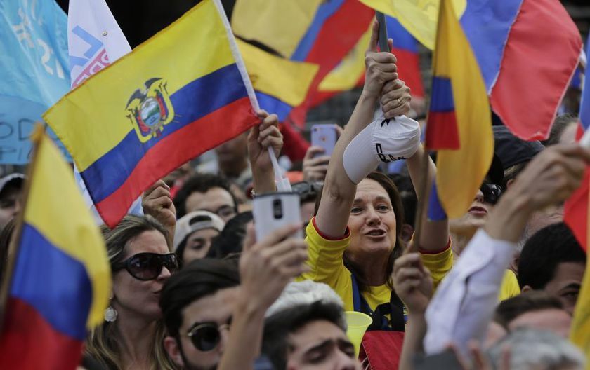 Supporters cheer on CREO's presidential candidate Guillermo Lasso outside the Electoral National Council, in Quito, Ecuador, Tuesday, Feb. 21, 2017. The Andean country is headed to a presidential runoff as ruling party candidate Lenin Moreno faces off against Lasso, a conservative former banker. (AP Photo/Dolores Ochoa)