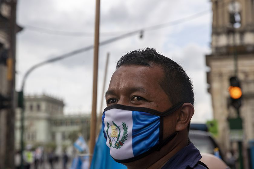A street vendor wearing a protective face mask with the colors of the Guatemalan flag, as a precaution against the spread of the new coronavirus, stands near Constitution square before the independence day celebration in Guatemala City, Monday, Sept. 14, 2020. Guatemala and Central America are celebrating 199 years of independence from Spain. (AP Photo/Moises Castillo)