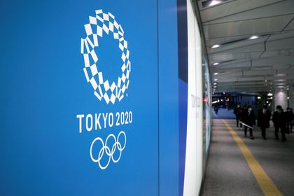 A man wearing a protective mask in front of an advertising billboard of Tokyo Olympics 2020, near the Shinjuku station in Tokyo