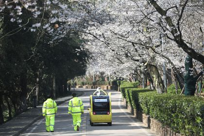 Security personnel walk next to a 5G enabled autonomous vehicle, installed with a camera filming blooming cherry blossoms for an online live-streaming session, inside the closed Wuhan University