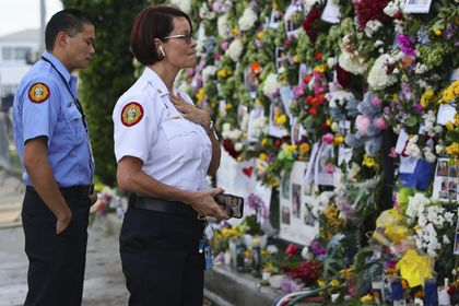 From left, Miami-Dade Fire Rescue personnel Fai Yeung and Chief Melanie C. Adams visit the makeshift memorial setup near the partially collapsed 12-story Champlain Towers South Condo in Surfside, Fla., Thursday, July 1, 2021. Search is paused because of structural concerns officials say. The apartment building partially collapsed on Thursday, June 24. (David Santiago /Miami Herald via AP)