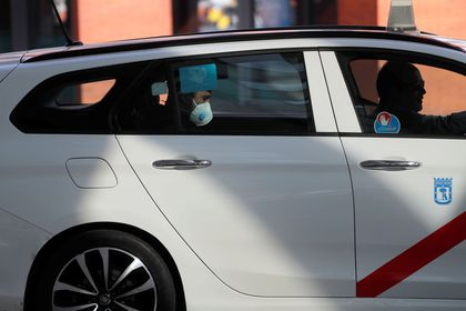 A man wearing a protective face mask rides in a taxi during partial lockdown as part of a 15-day state of emergency to combat the coronavirus disease outbreak in Madrid