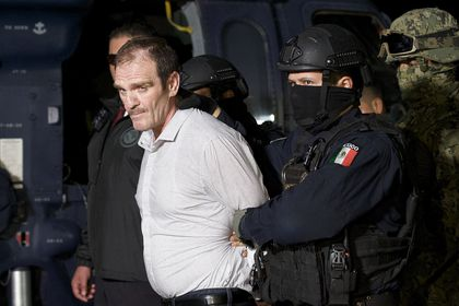 """FILE - In this June 15, 2016 file photo provided by the Mexican Attorney General's Office, Hector """"El Guero"""" Palma, is escorted in handcuffs from a helicopter at a federal hanger in Mexico City. An appeals court on Tuesday, July 13, 2021, in Mexico, has overturned Palma´s acquittal, and was taken to the country´s maximum security Altiplano prison after the ruling. (Mexico's Attorney General's Office via AP, File)"""
