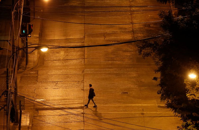 A man crosses an empty street, as most people stay at home amid the coronavirus disease (COVID-19) outbreak, in Vina del Mar
