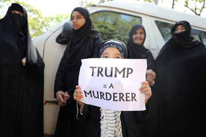 A girl holds a sign reading ?Trump is a murderer? during a condolence ceremony for Iranian Major-General Qassem Soleimani, who was killed in a airstrike near Baghdad, outside the Embassy of Iran in Kuala Lumpur