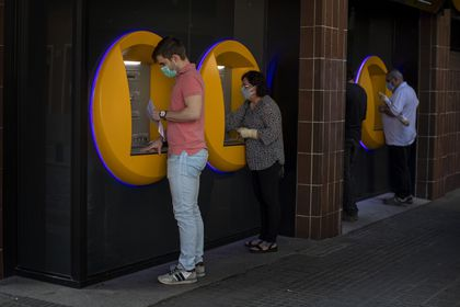 FILE - In this May 5, 2020, file photo, people wearing face masks use cash machines in Caldas de Montbui, near Barcelona, Spain. The coronavirus pandemic has reawakened debate about the continued viability of what has been the physical lifeblood of global economies: paper money and coins. (AP Photo/Emilio Morenatti)