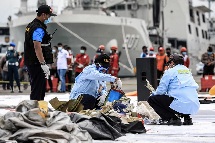 FILED - 10 January 2021, Indonesia, Jakarta: National Transportation Safety Committee and Disaster Victim Identification (DVI) police officers look through a bag of suspected debris near the crash site of the Sriwijaya Air flight SJ182 at Tanjung Priok port following the crash of a Boeing 737-500 passenger plane with 62 people on board. Photo: Risa Krisadhi/SOPA Images via ZUMA Wire/dpa Risa Krisadhi/SOPA Images via ZU / DPA 10/01/2021 ONLY FOR USE IN SPAIN