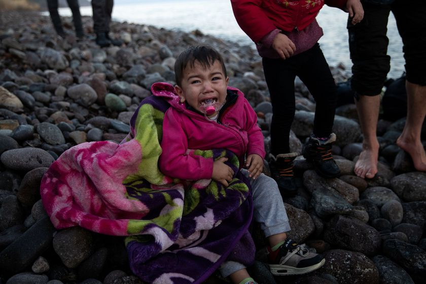 A child cries as migrants from Afghanistan arrive on a dinghy on a beach near the village of Skala Sikamias, after crossing part of the Aegean Sea from Turkey to the island of Lesbos