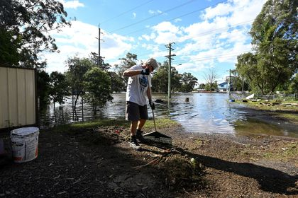 A man cleans up debris in front of his house in the suburb of Windsor as the state of New South Wales experiences widespread flooding and severe weather, near Sydney, Australia, March 24, 2021.  REUTERS/Jaimi Joy