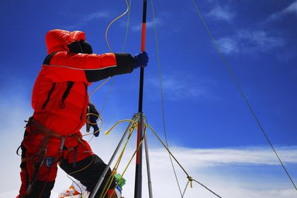 FILE - In this May 27, 2020, file photo released by Xinhua News Agency, a member of a Chinese surveying team sets up a survey equipment on the summit of Mount Everest also known locally as Mt. Qomolangma. China and Nepal have jointly announced on Tuesday, Dec. 8, 2020, a new height for Mount Everest, ending a discrepancy between the two nations. (Tashi Tsering/Xinhua via AP, File)