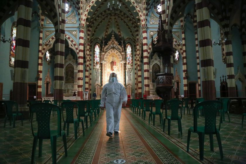 24 September 2020, Colombia, Bogota: A man in a protective suit walks through the a church after churches have been reopened to worshippers in Colombia following a long closure due to the coronavirus pandemic. Photo: Camila Diaz/colprensa/dpa