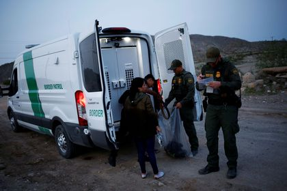 FILE PHOTO: Migrants from Central America who were detained hand over their belongings to U.S. Border Patrol agents after crossing into the United States from Mexico, in Sunland Park, New Mexico, U.S., July 22, 2021. REUTERS/Jose Luis Gonzalez/File Photo