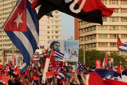 FILE PHOTO: People carry a poster with photographs of Cuba's late President Fidel Castro, Cuba's President and First Secretary of the Communist Party Miguel Diaz-Canel and Cuba's former President and First Secretary of the Communist Party Raul Castro during a rally in Havana, Cuba, July 17, 2021. REUTERS/Alexandre Meneghini/File Photo