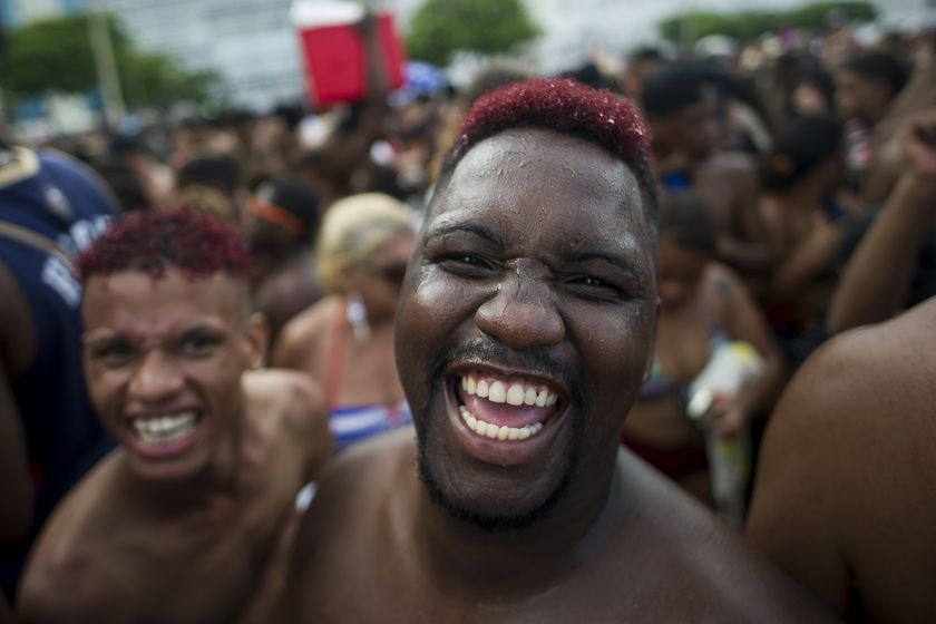 "FILE - in this Jan. 12, 2020 file photo, revelers smile as they look on the camera during the ""Bloco da Favorita"" street party on Copacabana beach, Rio de Janeiro, Brazil. The city announced on Thursday, Sept. 24, said it has delayed its annual Carnival parade, saying the global spectacle cannot go ahead in February because of Brazil's continued vulnerability to the new coronavirus pandemic, but has yet to announce a decision about the Carnival street parties that take place across the city.  (AP Photo/Bruna Prado, File)"