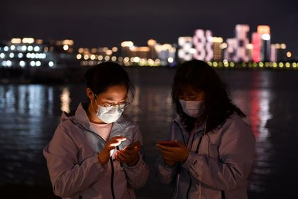 Medical workers from outside Wuhan check their mobile phones at a riverside park in Wuhan