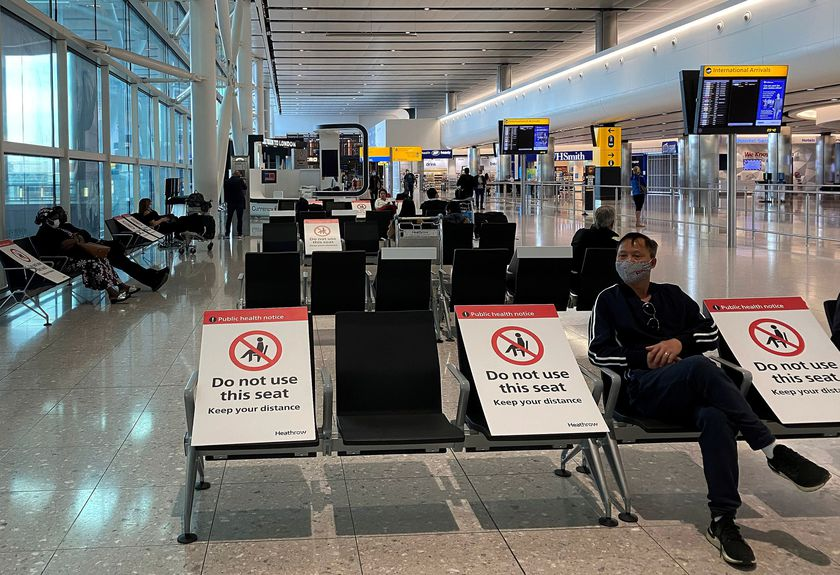 People sit amongst socially-distanced seating signs at Heathrow Airport in London