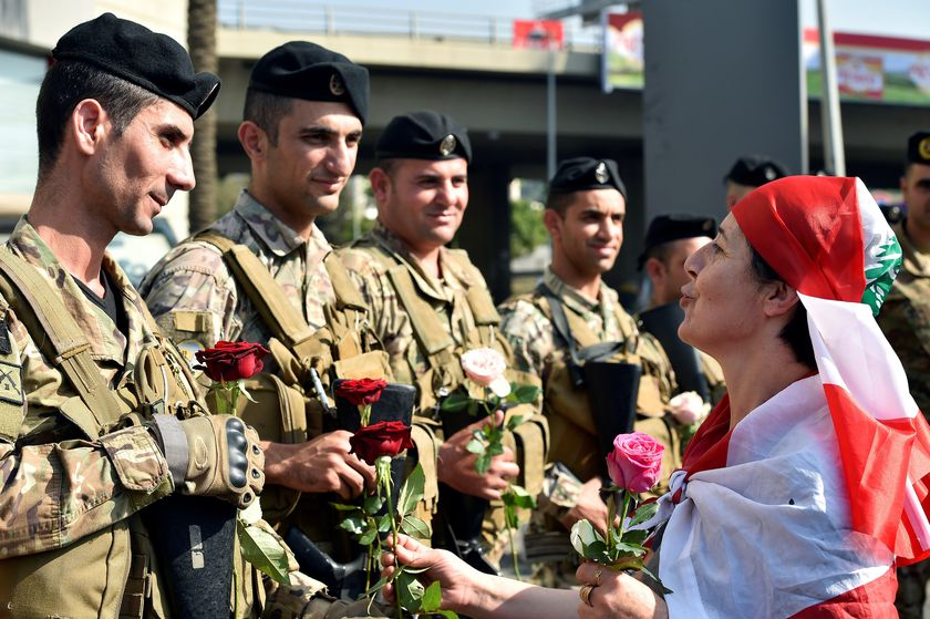 Lebanese anti-government protesters offer flowers to army soldiers