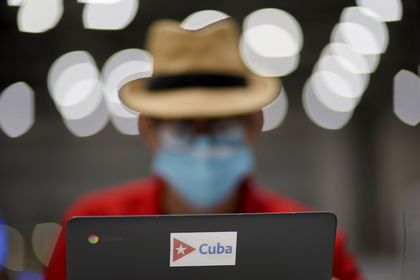 Norland Rosendo Gonzalez, a journalist with Periodico Juventud Rebelde in Cuba, works in the main press center at the 2020 Summer Olympics, Tuesday, July 20, 2021, in Tokyo. (AP Photo/David Goldman)