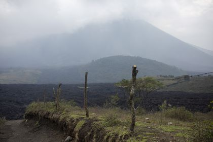 Shrouded by clouds and volcanic ash particles, lava flows down the slopes of the Pacaya Volcano, near El Patrocinio village in San Vicente Pacaya, Guatemala, Wednesday, April 21, 2021. The 8,373-foot volcano, just 30 miles south of Guatemala's capital, has been active since early February. (AP Photo/Moises Castillo)