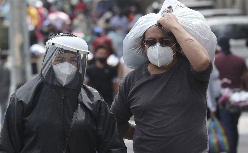 People wearing masks and face shields walk in the capital's downtown amid the new coronavirus pandemic in Quito, Ecuador, Monday, June 29, 2020. (AP Photo/Dolores Ochoa)