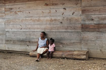 Duperat Laurette sits on a log with a girl at the entrance of a migrant shelter in Lajas Blancas, Darien province, Panama, Saturday, Aug. 29, 2020. The 45-year-old Haitian migrant and her husband emerged from the thick jungle that blankets the Panama-Colombia border here in Darien seven months earlier and have advanced no farther because of the new coronavirus pandemic. (AP Photo/Arnulfo Franco)