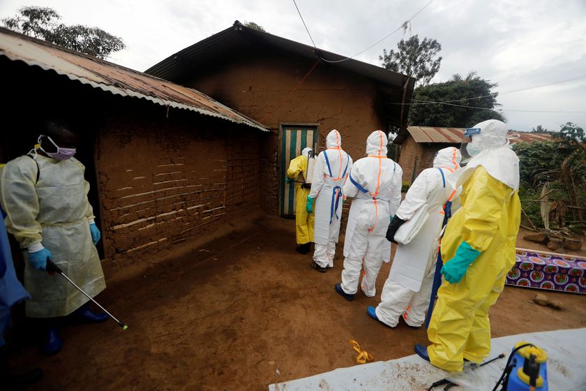 FILE PHOTO: Kavota Mugisha Robert (L), a healthcare worker who volunteered in the Ebola response, stands with decontamination gear as his colleague prepare to enter a house where a woman, 85, is suspected of dying of Ebola in the Eastern Congolese town of