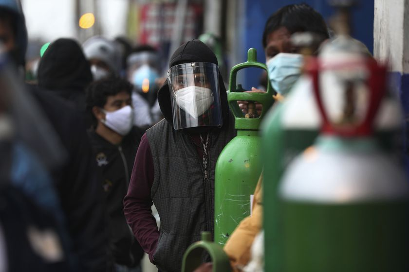 People wait in line with their empty oxygen cylinders to refill at a shop in the San Juan neighborhood of Lima, Peru, Monday, Aug. 3, 2020. Peruvian authorities calculate that more than a quarter of Lima's population may have been infected with the new coronavirus, and Peru has the highest death rate per million in the Americas. (AP Photo/Martin Mejia)