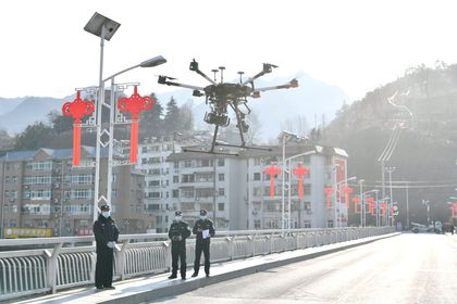 Police officers operate a drone to spread information about the prevention and control of the new coronavirus, in Baokang