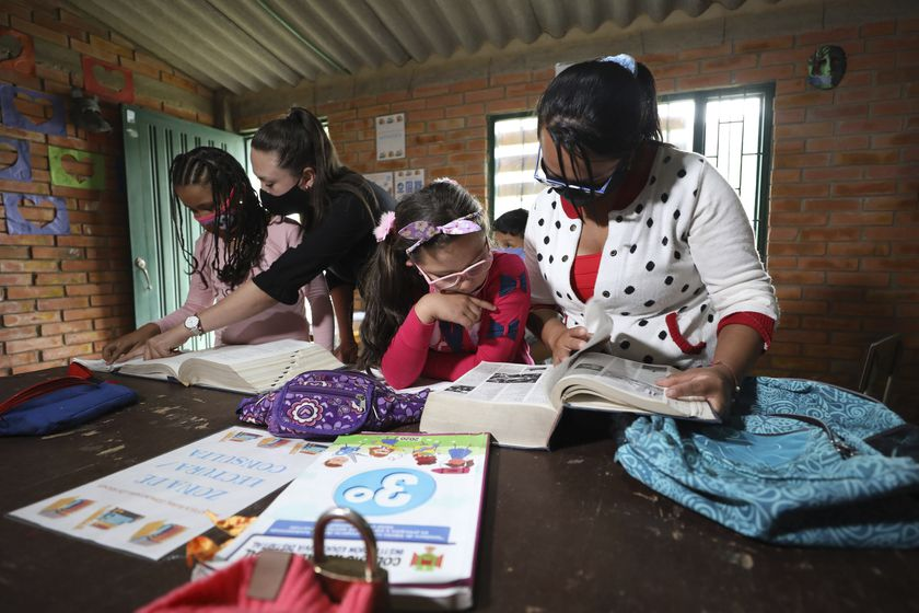 Ana Milena Liberato, right, reads a book with her daughter Wendy Valeria, as they do her biology homework at Los Soches Rural Community Library in Los Soches, a small rural village on the outskirts of Bogota, Colombia, Wednesday, Feb. 10, 2021. Every month Liberato must allocate 50,000 pesos (approximately 15 dollars) to buy internet packages, although in the middle of the new coronavirus pandemic she lost her job. (AP Photo/Fernando Vergara)