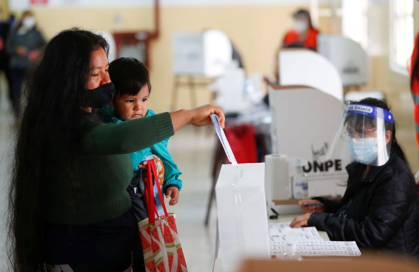 A Peruvian woman residing in Argentina holds a baby as she casts her vote at a polling station in a public school, in Peru's presidential election, in Buenos Aires, Argentina April 11, 2021. REUTERS/Agustin Marcarian