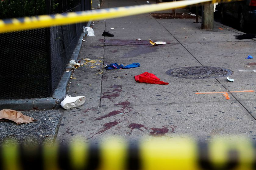 A blood stained sidewalk and clothing are seen behind NYPD police tape, where according to local media reports five people were shot, including a 6-year-old boy, early Monday during an outdoor J?Ouvert celebration, in the Crown Heights section Brooklyn i