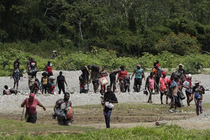 Migrants cross the Tuquesa river after a trip on foot through the jungle to Bajo Chiquito, Darien province, Panama, Wednesday, Feb. 10, 2021. Bajo Chiquito is the first population center that migrants coming from the Colombian border see when they cross over after several days of slogging through the jungle into Panama. (AP Photo/Arnulfo Franco)