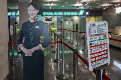 Human-sized flight attendant dummies are seen on display at an empty check-in counter for Evergreen Airways at Taipei Songshan Airport in Taipei
