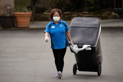 A worker carries a garbage can while wearing a mask at the Life Care Center of Kirkland, where two of three confirmed coronavirus cases in the state had links to the long-term care facility in Kirkland