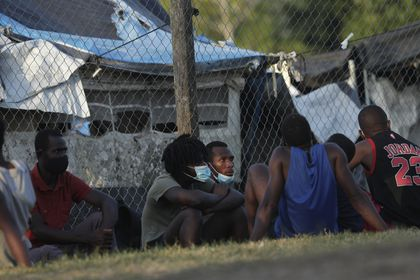 Haitian migrants sit on the grass at a migrant camp amid the new coronavirus pandemic in San Vicente, Darien province, Panama, Tuesday, Feb. 9, 2021. Panama is allowing hundreds of migrants stranded because of the pandemic, to move to the border with Costa Rica, after just reopening its land borders. (AP Photo/Arnulfo Franco)