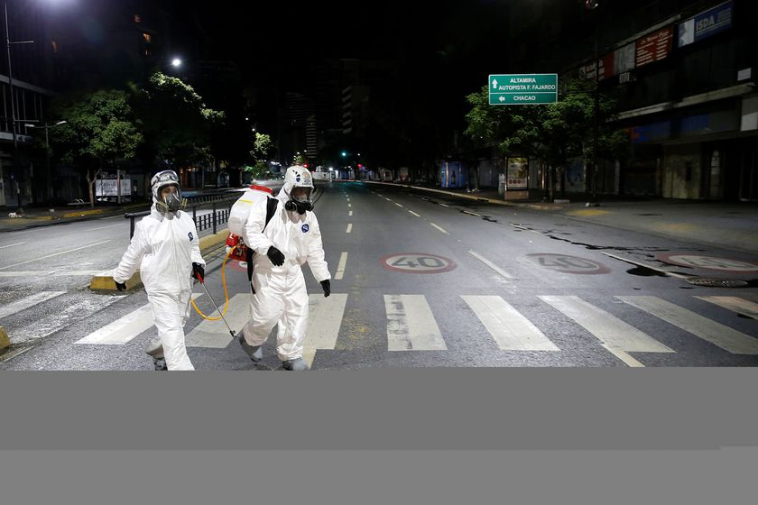 Workers in protective suits walk on the street during the national quarantine in response to the spread of coronavirus disease (COVID-19) in Caracas