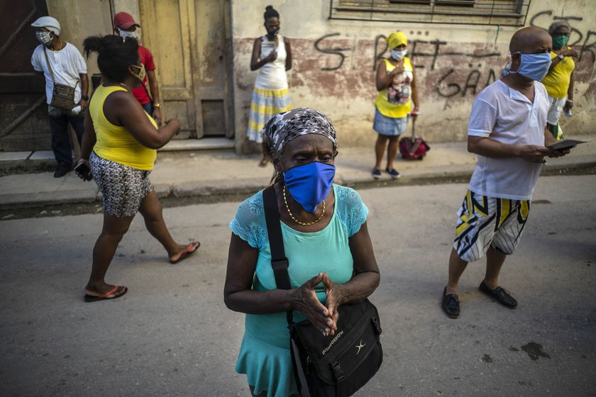 People wearing face masks amid the new coronavirus pandemic pray during a Catholic Mass broadcast by radio in honor of the Virgin of Charity of Cobre, on her feast day in Havana, Cuba, Tuesday, Sept. 8, 2020. The virgin is Cuba's Catholic patron saint. (AP Photo/Ramon Espinosa)