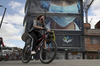 Women wearing protective face masks pedal past on bicycles in Bogota, Colombia, Thursday, July 23, 2020, amid the new coronavirus pandemic. As COVID-19 cases in Colombia continue to climb, the mayor of Bogota has imposed social distancing measures. (AP Photo/Fernando Vergara)