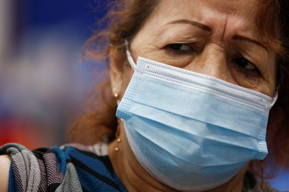 A woman reacts as she receives the first dose of China's Sinovac Biotech vaccine against the coronavirus disease (COVID-19), during a mass vaccination program for the elderly, at the Bolivarian Technology Institute in Guayaquil, Ecuador April 15, 2021. REUTERS/Santiago Arcos