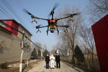 Volunteer in protective suits controls a drone to spray disinfectants at Zhengwan village, as the country is hit by an outbreak of the new coronavirus, in Handan