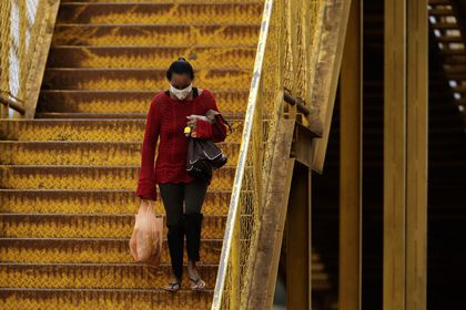 A woman wearing a mask against the spread of the new coronavirus walks down a set of stairs in Valparaiso, Brazil, Wednesday, May 20, 2020. Valparaiso, 40 km. from Brasilia, appears in the statistics as one of the cities in the state of Goias with a high incidence of COVID-19. (AP Photo/Eraldo Peres)