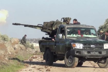 A still image shows a Syrian army soldiers firing a weapon as they advance on the town of Kfar Nabl