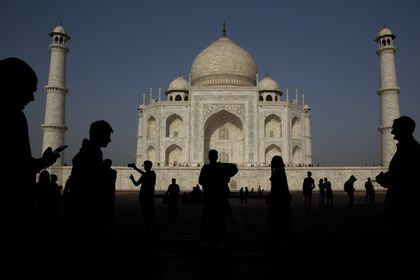 FILE - In this Sunday, March 24, 2019, file photo, tourists visit the Taj Mahal monument, in Agra, India. India reopened to fully vaccinated foreign tourists traveling on chartered flights on Friday, Oct. 15, 2021, in the latest easing of its coronavirus restrictions as infection numbers decline. Foreign tourists on regular flights will be able to enter India starting Nov. 15. (AP Photo/Manish Swarup)
