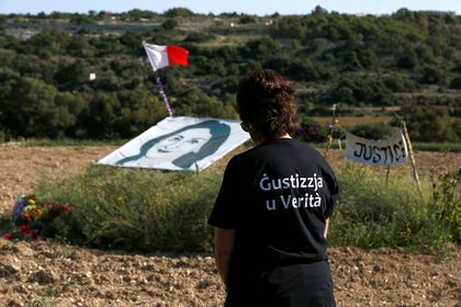 A woman is seen in front of a banner depicting anti-corruption journalist Daphne Caruana Galizia during a commemoration at the site where the journalist was assassinated with a car bomb three years ago, in Bidnija, Malta October 16, 2020. REUTERS/Darrin Zammit Lupi